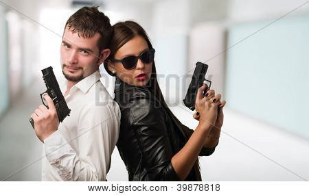 Young Couple Holding Gun against an abstract background