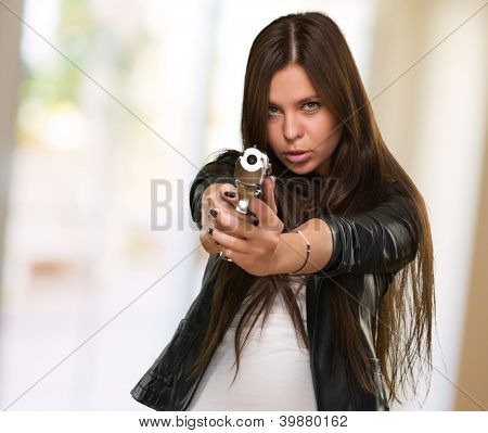 Portrait Of A Woman Holding Gun against an abstract background