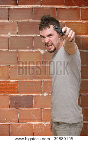 furious man pointing with gun against a brick wall