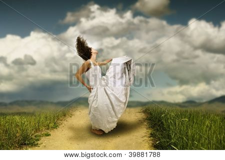 a runaway bride dancing on a path in a meadow