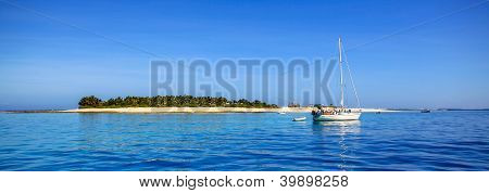 Boat and beautiful Fiji atoll island with white beach