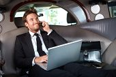 stock photo of limousine  - Smiling handsome businessman sitting in luxury limousine - JPG