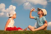 stock photo of drinking water  - Boy and girl sit on grass and drink from bottle - JPG
