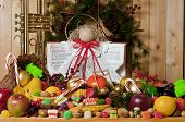 stock photo of angel-trumpet  - song book angel and brass trumpet surrounded by a cornucopia of  fruits and chriistmas candy - JPG