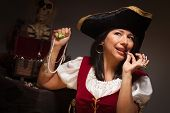 picture of wench  - Dramatic Female Pirate Biting a Coin in a Dimly Lit Moody Scene - JPG