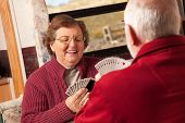 stock photo of trailer park  - Happy Senior Adult Couple Playing Cards in Their Travel Trailer RV - JPG