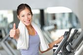 stock photo of treadmill  - Happy fitness woman thumbs up in gym during exercise training on moonwalker treadmill - JPG