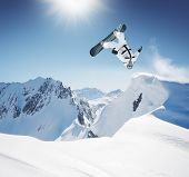 stock photo of snowboarding  - Snowboard Jumping in high mountains - JPG