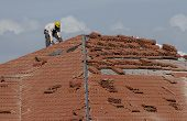 image of commercial building  - Employee working on a roofing project with ceramic shingles in daylight - JPG
