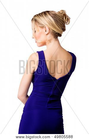 back of a young beautiful woman with upstyle blond hair wearing tight blue evening dress on her fit slim body over white studio background