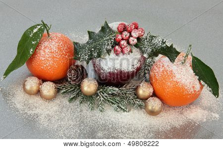 Christmas decoration with apple and mandarin orange fruit over silver grey background.