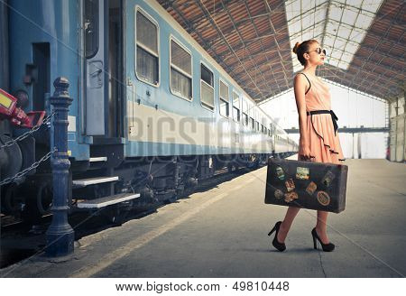 fair traveler with vintage suitcase at the station