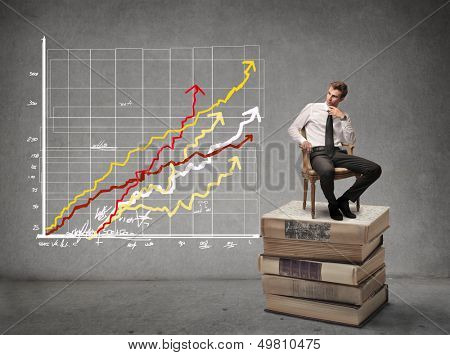business man sitting on stack of books looks chart