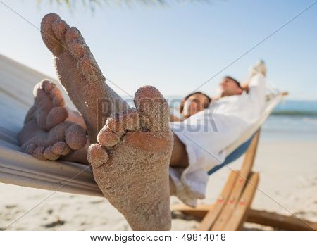 Close up of sandy feet of couple in a hammock on the beach