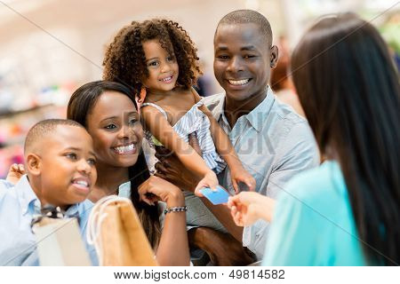 Happy shopping family at the cashier paying for their purchases