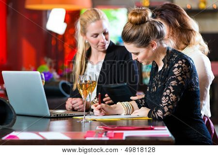 Young women or colleagues in cafe or restaurant, they working together and having fun, they are a good team
