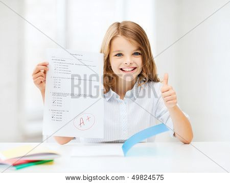 education and school concept - little student girl with test and A grade showing thumbs up at school