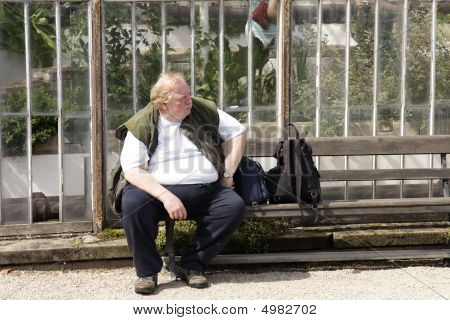 Large Man Sitting On A Bench