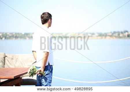 Handsome with bouquet of roses man waiting a woman
