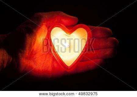 burning candle heart on hand