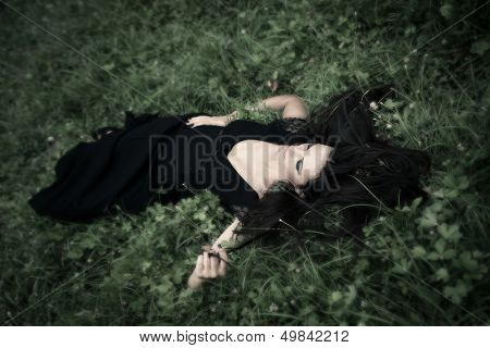 elegant  woman in long black dress lie in grass  full body shot