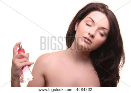 Attractive Brunette Applying Perfume On White Background