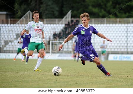 KAPOSVAR, HUNGARY - AUGUST 16: Simon Ligot (in purple) in action at a Hungarian National Championship soccer game - Kaposvar (white) vs Ujpesti TE (purple) on August 16, 2013 in Kaposvar, Hungary.