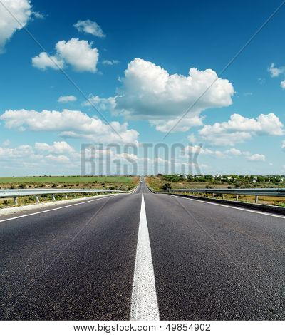 black asphalt road to horizon under deep blue cloudy sky