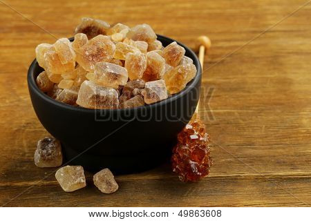 Rock candy sugar in a cup on wooden table