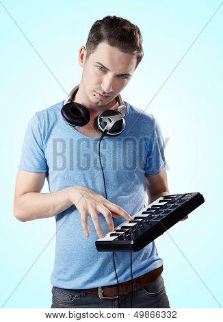 Deejay With Headphones Pressing Keys On Midi Keyboard