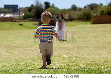 Toddler running towards his mother