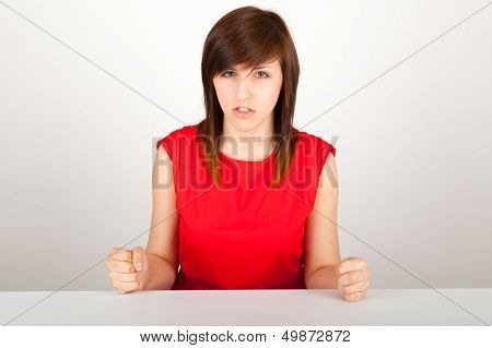 The Young Woman Is Angrily Sitting At The Table