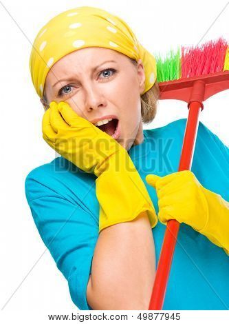 Young woman - cleaning maid with broom holding her face in astonishment, isolated over white
