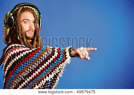Portrait of a rastafarian young man listening to music in headphones and  pointing the finger somewhere.