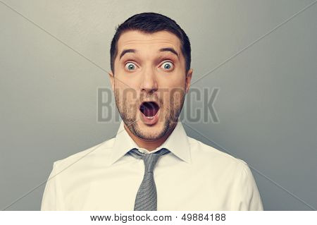 portrait of confused businessman wit open mouth over grey background