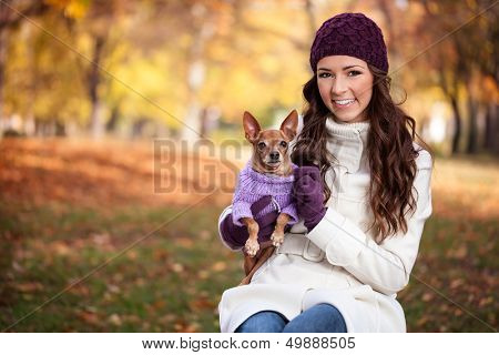 Happy woman holding her little dog in arms