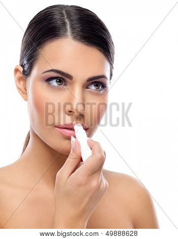 Young woman applying balsam on lips