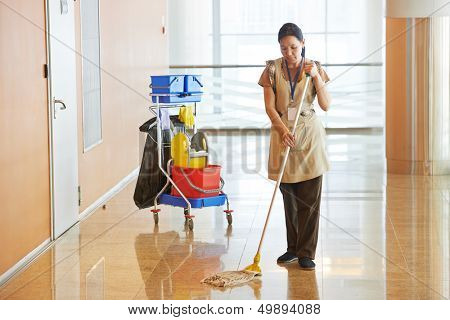 Female cleaner maid woman worker with mop in uniform cleaning corridor pass or hall floor of business building