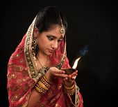 Beautiful young Indian woman in traditional sari dress holding a diwali oil lamp light, isolated on