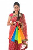 Portrait of beautiful young Indian woman in traditional sari dress holding shopping bags, standing i
