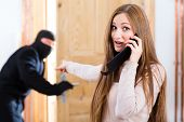 Security - disguised burglar breaking in an apartment or office, a woman calling the police with her