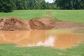 image of sedimentation  - a pile of mud behind a pool of muddy water - JPG
