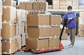 stock photo of pallet  - Male chinese worker with fork pallet truck stacker in warehouse loading group of boxes packages - JPG