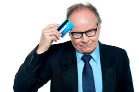 foto of thinkers pose  - Pensive looking businessman scratching his forehead with credit card over white background - JPG