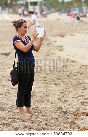 Woman Uses Tablet Computer To Capture Family Images On Beach