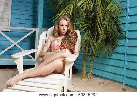 sexy young woman in bikini standing in beach bungalow