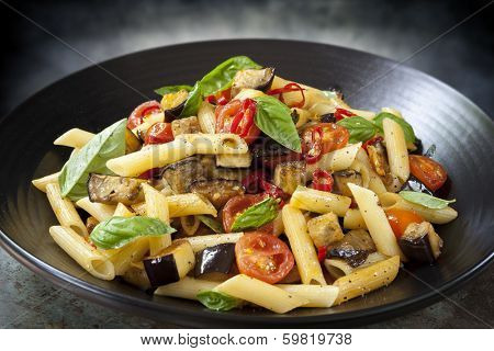 Eggplant, chilli and tomato penne pasta, on a black serving platter.  Garnished with basil.