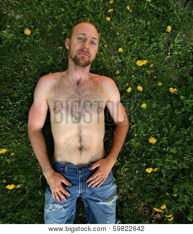 a shirtless man surrounded by weeds