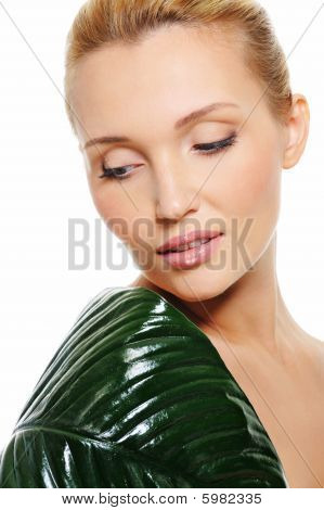 Young Beautiful Woman With Green Leaf Covering Her Shoulder