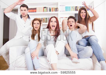 Divided Friends Watching Game Cheering For Different Teams